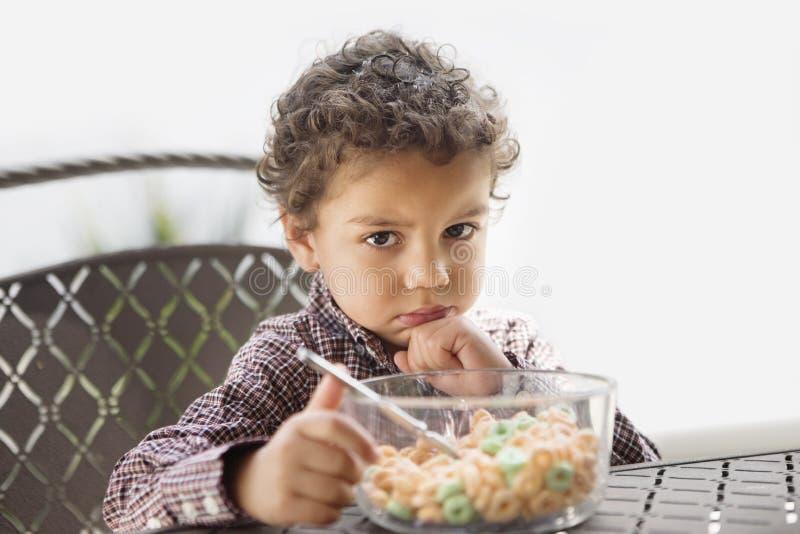 Criança mal-humorada desapontado com seu café da manhã fotografia de stock royalty free