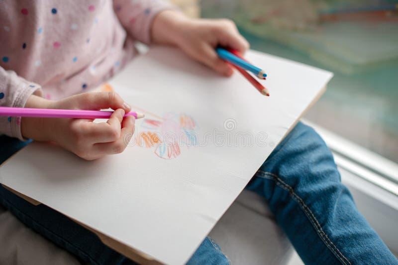 A criança mantém sua imagem em seus joelhos fotografia de stock royalty free