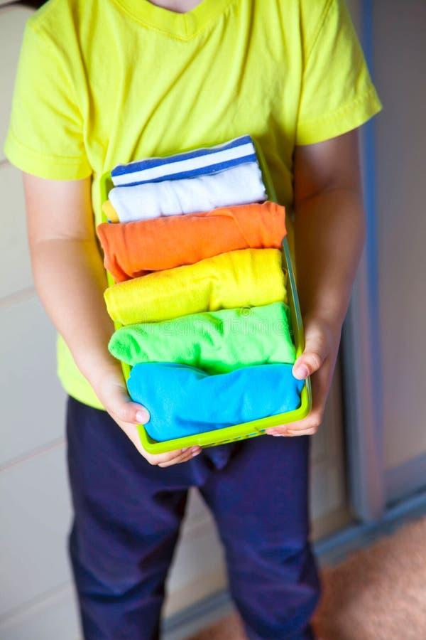 A criança mantém suas coisas O menino põe os t-shirt em um drawe imagem de stock royalty free