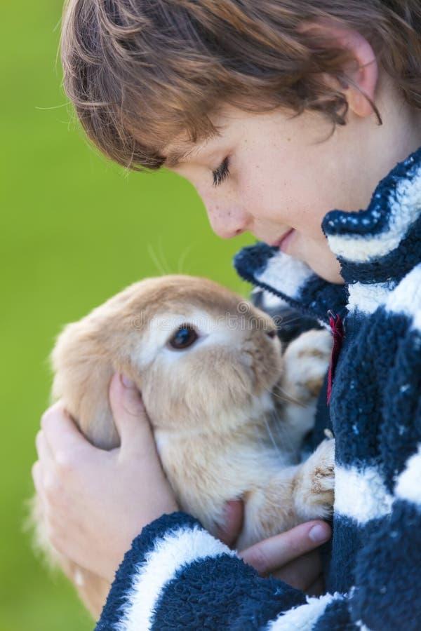 Criança masculina do menino que joga com coelho do animal de estimação imagem de stock