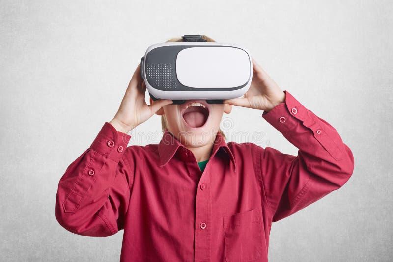 A criança masculina entusiasmado veste óculos de proteção virtuais do relaity, estando contente de ver as imagens fantásticas, vi imagem de stock royalty free