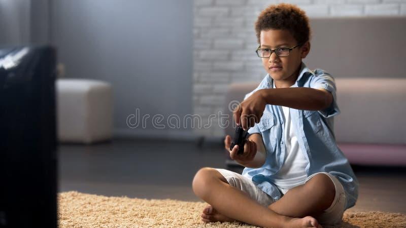 Criança masculina que joga na casa do console do jogo de vídeo, assoalho de assento, apego do dispositivo imagem de stock royalty free