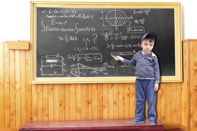 A criança menor escreve fórmulas complicadas no lackboard imagens de stock royalty free