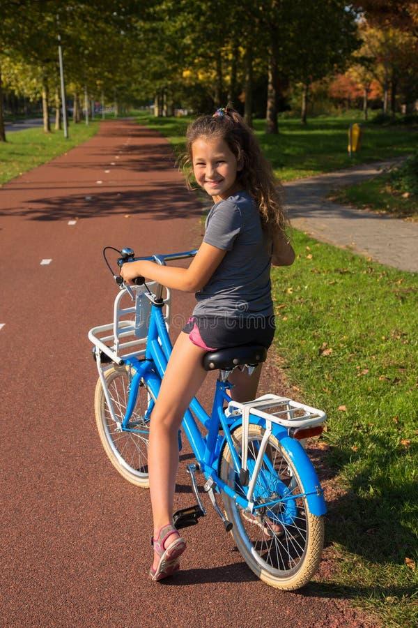 A criança monta a bicicleta no trajeto da bicicleta A menina está sorrindo, ela está feliz fotografia de stock