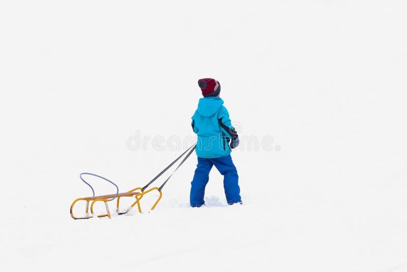 A criança monta no inverno em um trenó em uma rua nevado Atividade de crescer acima a geração no ar fresco Saudável foto de stock royalty free
