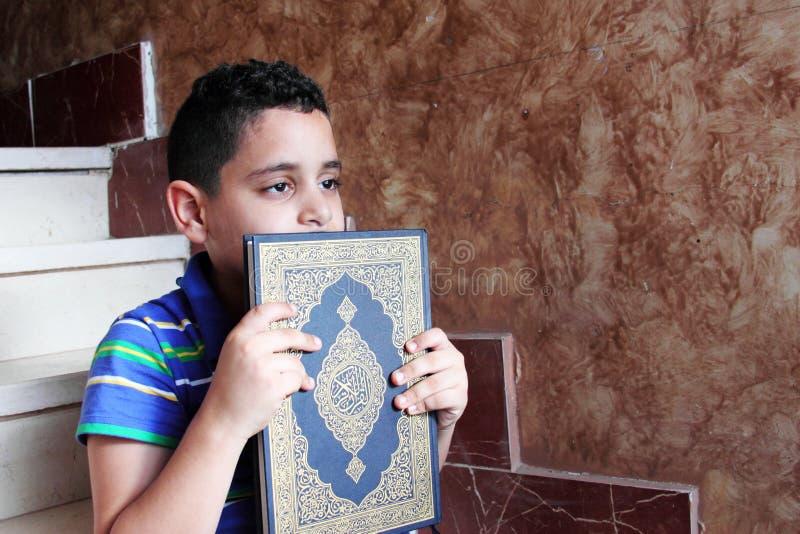 Criança muçulmana árabe com livro sagrado do koran imagens de stock royalty free
