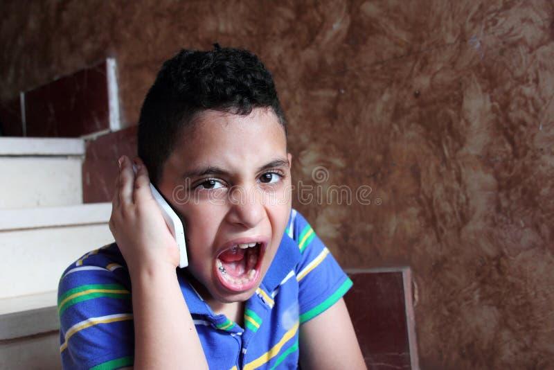 Criança muçulmana árabe irritada que fala no telefone celular foto de stock
