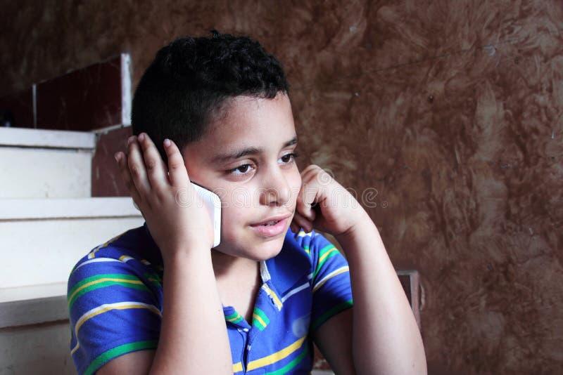 Criança muçulmana árabe que fala no telefone celular fotografia de stock royalty free