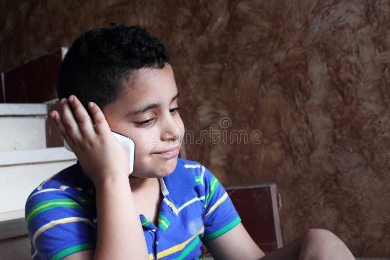 Criança muçulmana árabe que fala no telefone celular foto de stock