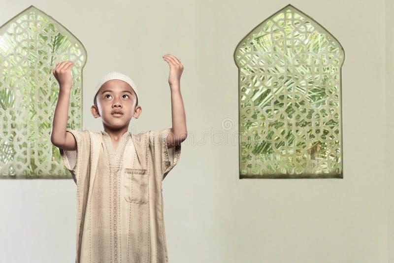 Criança muçulmana asiática religiosa que está rezando ao deus imagem de stock