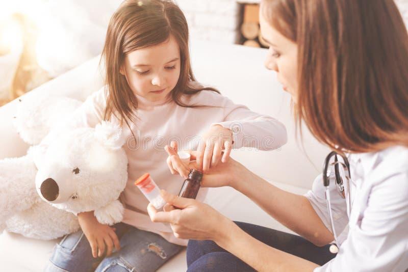 Criança muito séria que toma a tabuleta da mão de seu doutor foto de stock