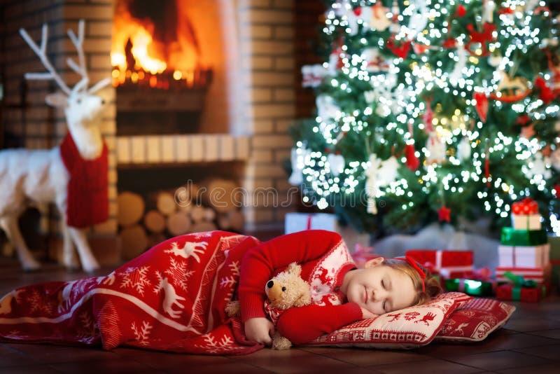 Criança na árvore de Natal Criança na chaminé no Xmas imagens de stock