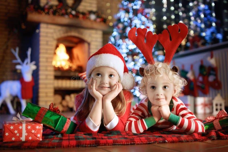 Criança na árvore de Natal Crianças na chaminé no Xmas fotos de stock