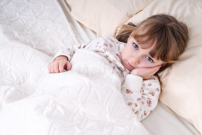 Criança na cama com mão no mordente fotografia de stock