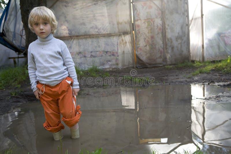 Criança na chuva embebida com água. foto de stock