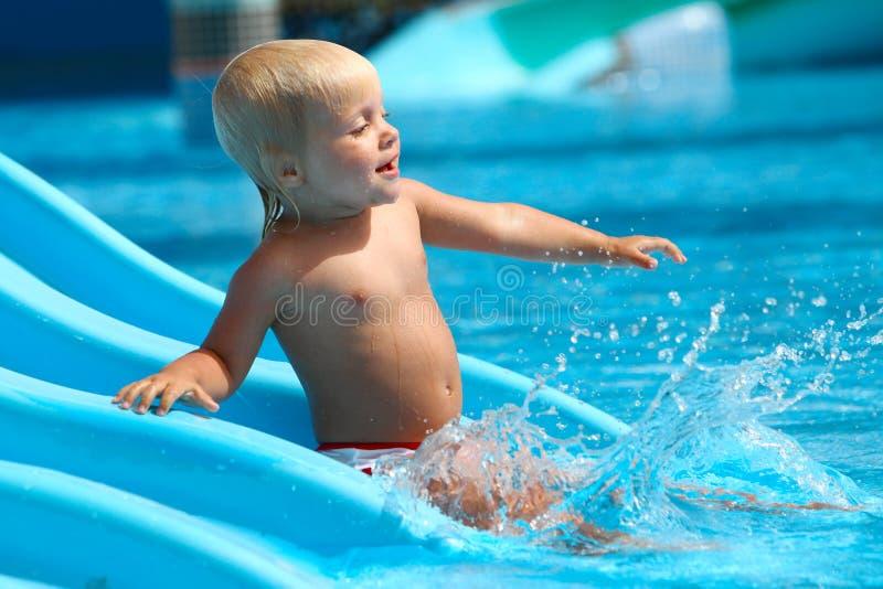 Criança na corrediça de água foto de stock