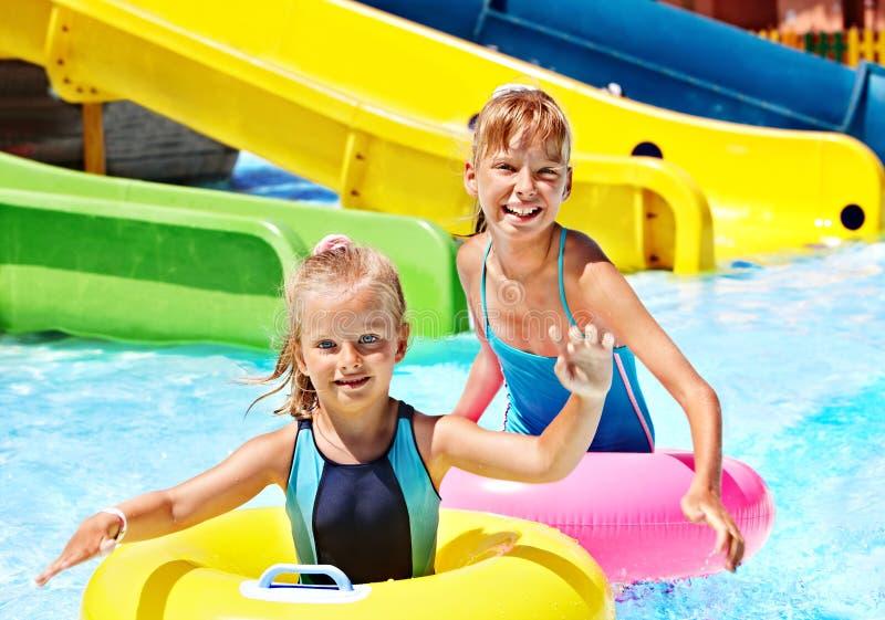 Criança na corrediça de água no aquapark. fotos de stock