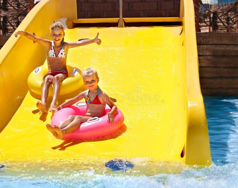Criança na corrediça de água no aquapark. imagens de stock