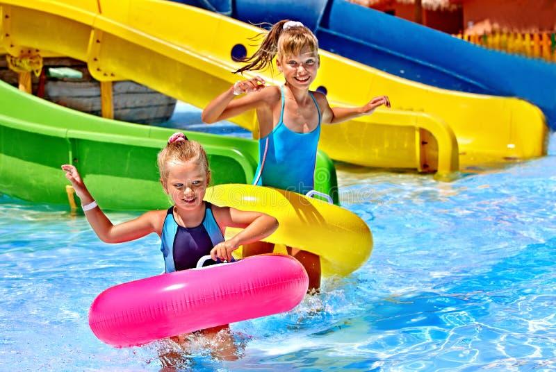Criança na corrediça de água no aquapark foto de stock