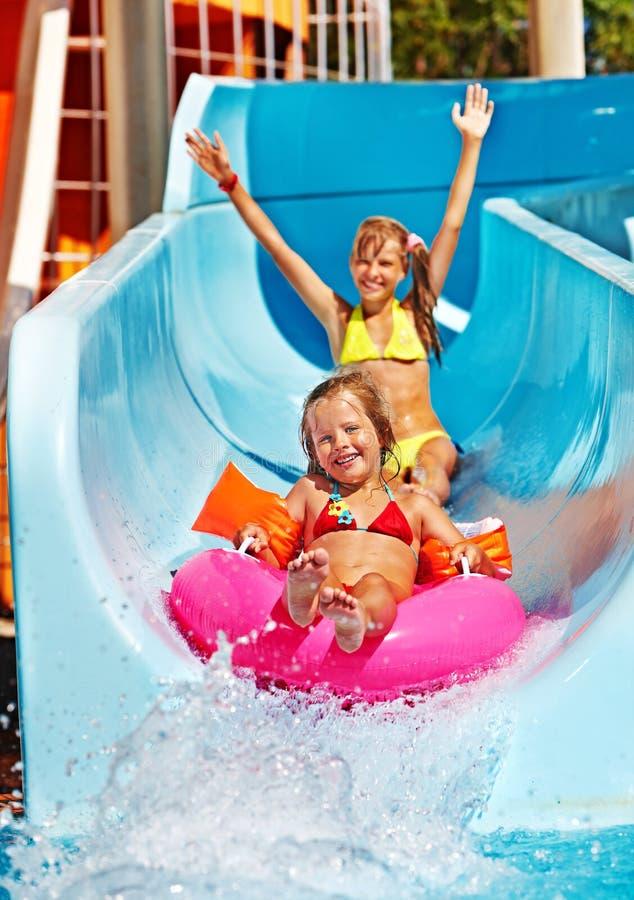 Criança na corrediça de água no aquapark imagens de stock