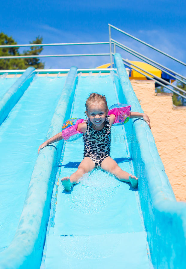 Criança na corrediça de água no aquapark durante o verão imagem de stock