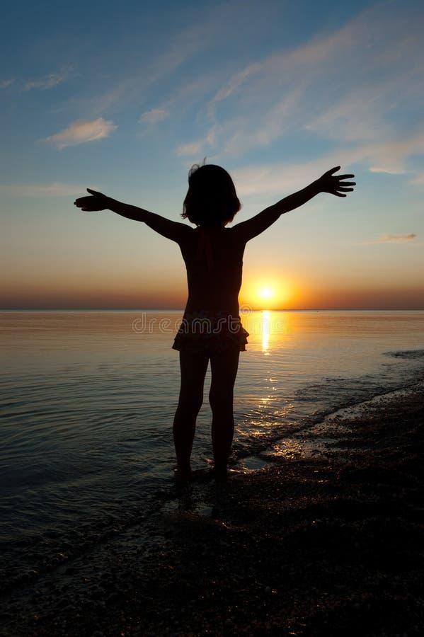 Criança na praia do por do sol foto de stock royalty free