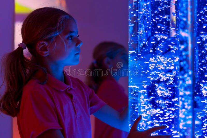 A criança na sala de estimulação sensorial da terapia, snoezelen Criança que interage com a lâmpada colorida do tubo de bolha das fotografia de stock royalty free