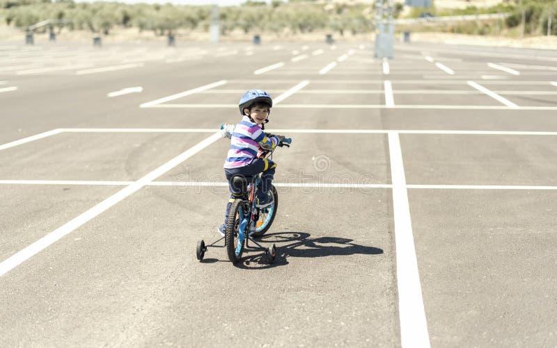 Criança na vista de estacionamento do riddingin da bicicleta para trás imagem de stock