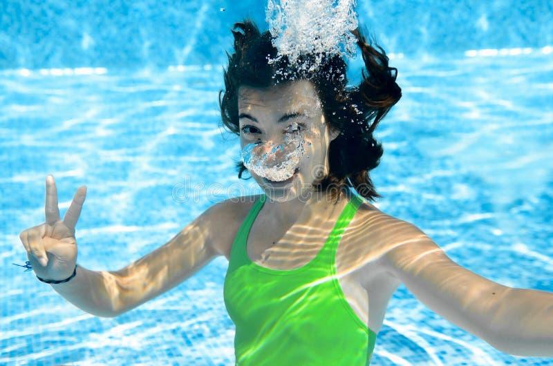 A criança nada no adolescente que ativo subaquático, feliz da piscina a menina mergulha e tem o divertimento sob a água, a aptidã fotografia de stock royalty free