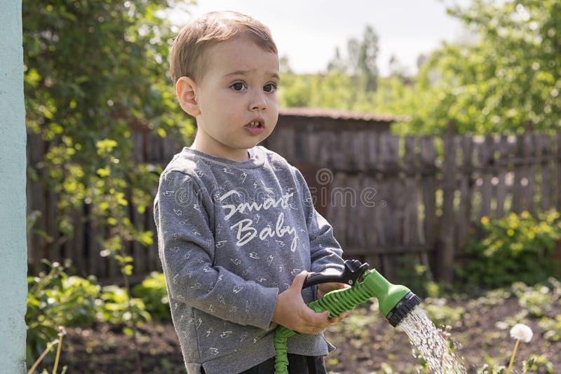 Criança nas flores molhando do jardim imagens de stock