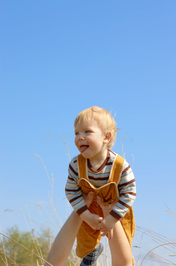 Criança nas mãos. fundo do céu fotografia de stock