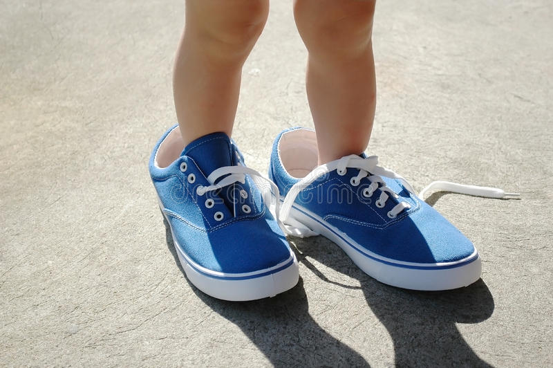 Criança nas sapatas azuis do adulto fotos de stock