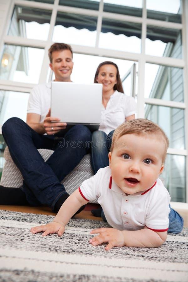 Criança no assoalho - pais que usam o portátil foto de stock