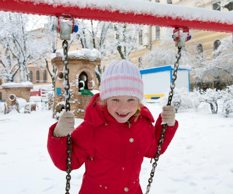 Criança no balanço no parque do inverno imagem de stock