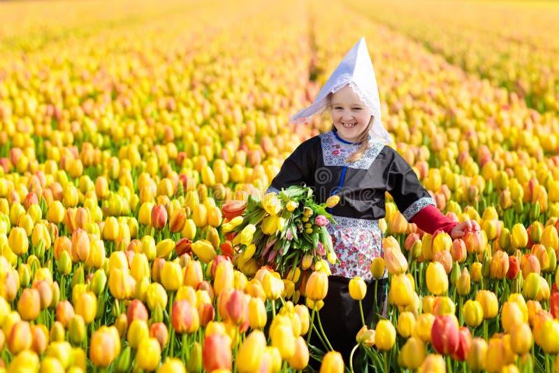 Criança no campo de flor da tulipa Moinho de vento em holland imagens de stock
