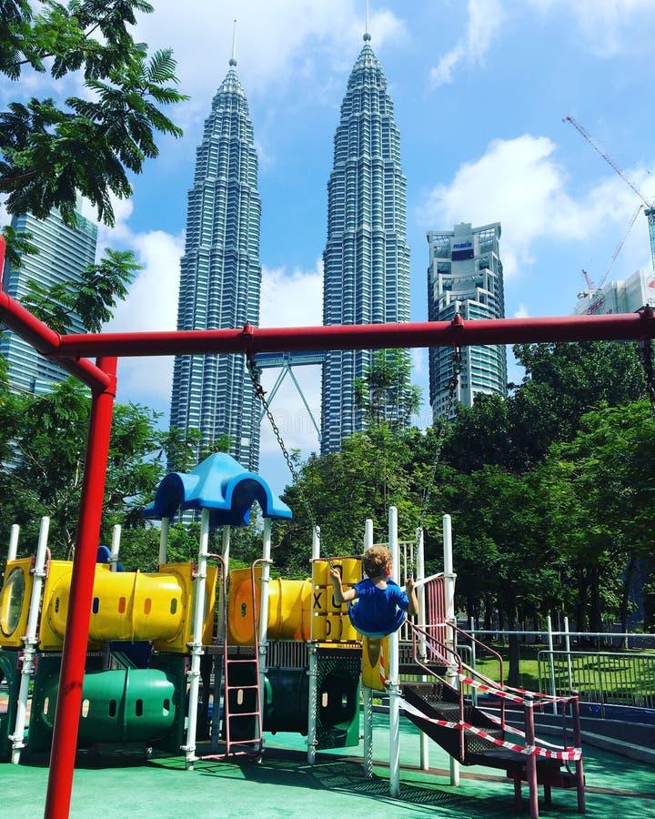 Criança no campo de jogos e nas torres gêmeas quilolitro de Petronas foto de stock royalty free