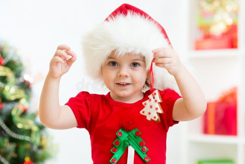 Criança no chapéu de Santa que guarda cookies do Natal foto de stock