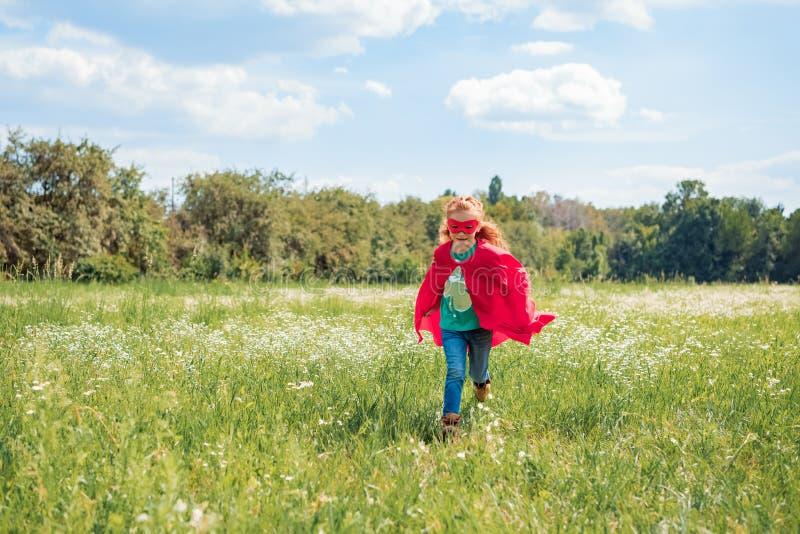 criança no corredor vermelho do cabo e da máscara do super-herói no prado imagens de stock