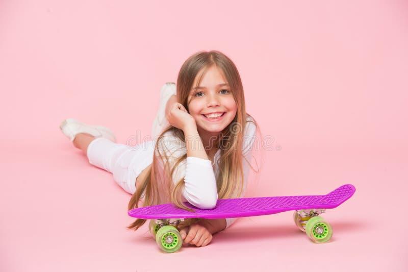 Criança no equipamento branco que encontra-se no assoalho Menina com o cabelo louro longo isolado no fundo cor-de-rosa Criança co foto de stock