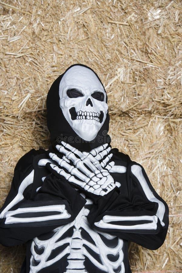 Criança no equipamento de esqueleto que está contra o feno imagens de stock