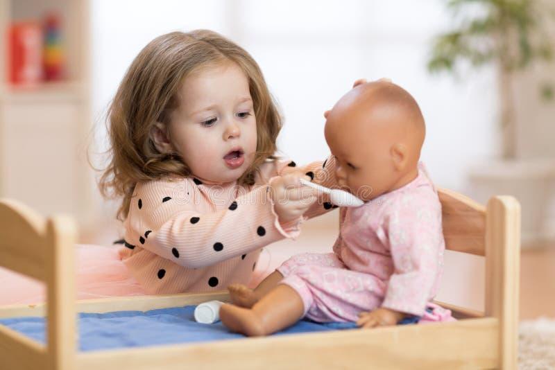 Criança no jardim de infância Criança no infantário Criança pequena que joga com boneca imagens de stock royalty free