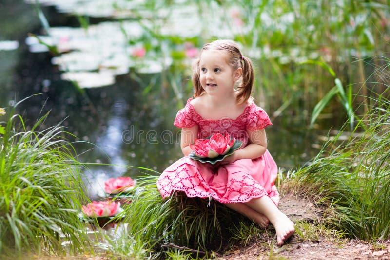Criança no lago com as flores do lírio de água foto de stock