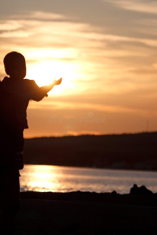 Criança no por do sol foto de stock royalty free