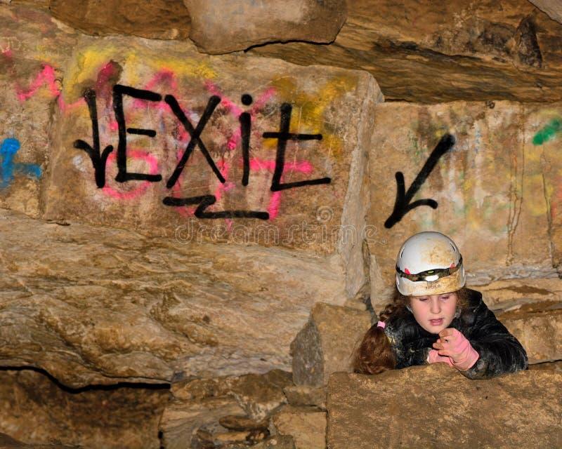 Criança no subterrâneo de escalada do capacete em uma mina, pelo sinal 'da saída' imagens de stock