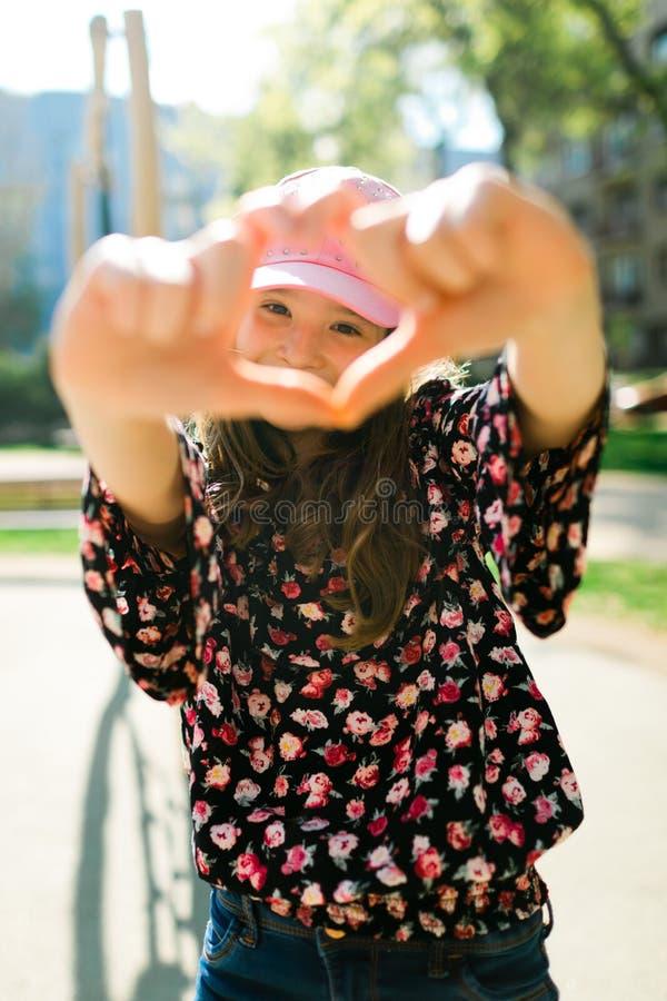 Criança no tampão cor-de-rosa que balança no campo de jogos - forma do coração imagem de stock