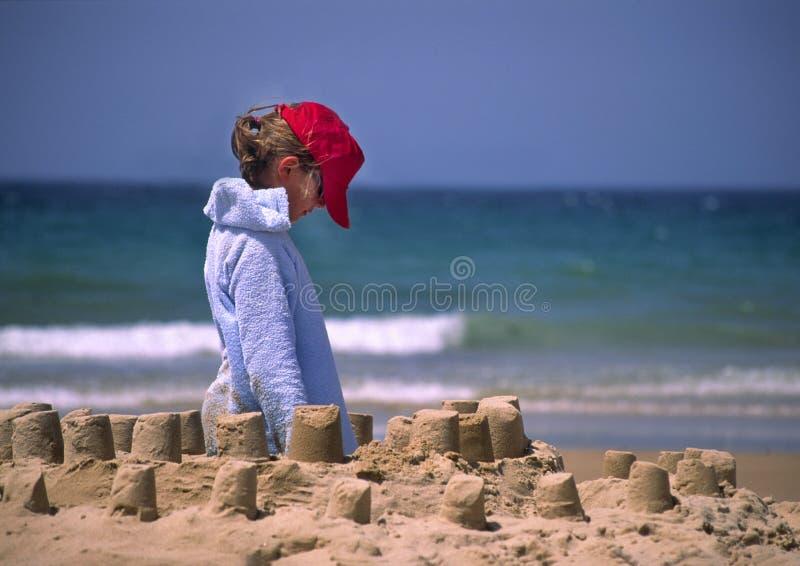 Criança no tampão vermelho na praia imagens de stock royalty free