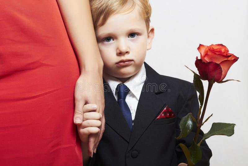 Criança no terno com mãe. flor. vestido vermelho. família. rapaz pequeno elegante. rosa do vermelho. tome a mão foto de stock