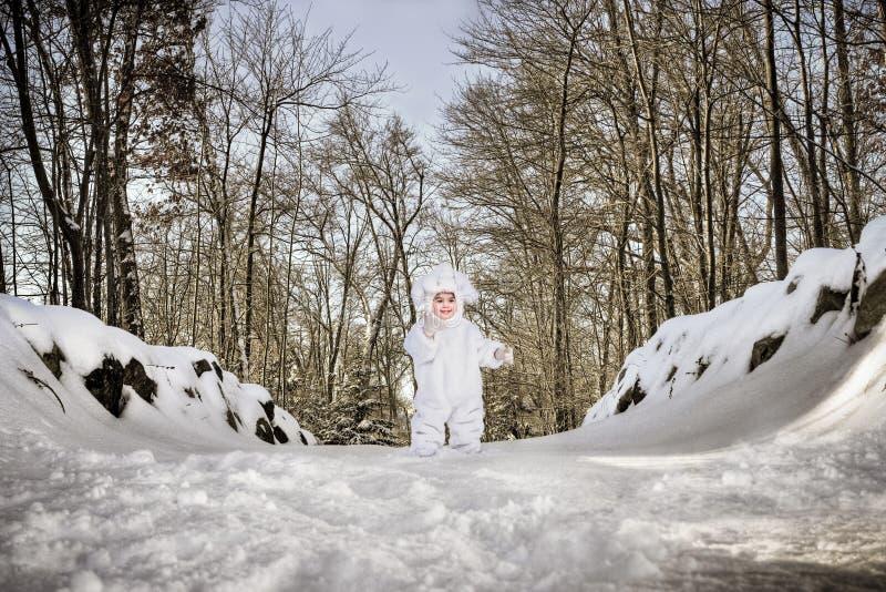 Criança no terno do coelho na neve foto de stock