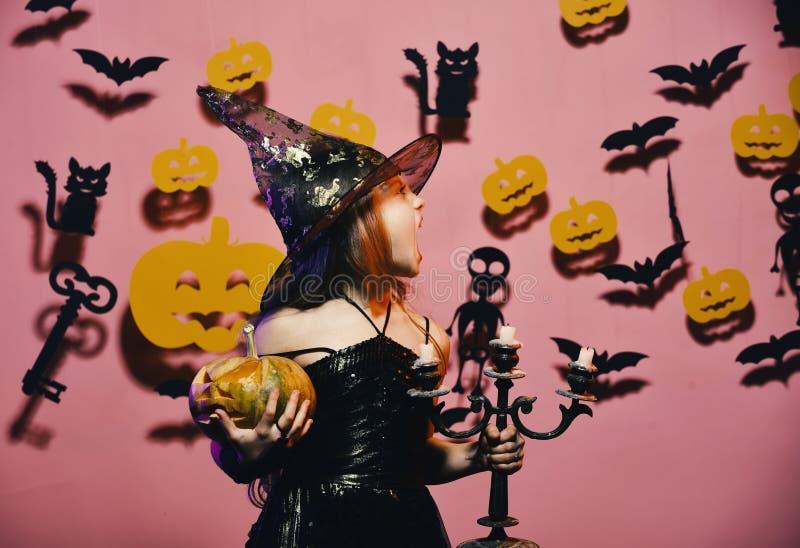 A criança no traje assustador das bruxas guarda a abóbora e o candelabro cinzelados fotos de stock