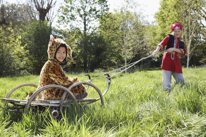 Criança no traje do pirata que puxa o menino no traje de Jaguar no carro fotos de stock